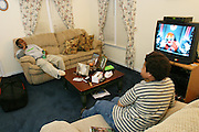 """(MODEL RELEASED IMAGE). Brandon and Tyrone (left) watch television, """"one of the downfalls,"""" says Tyrone, """"to getting exercise. (Supporting image from the project Hungry Planet: What the World Eats.) The Revis family of Raleigh, North Carolina, is one of the thirty families featured, with a weeks' worth of food, in the book Hungry Planet: What the World Eats."""