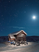 Snowmobiles parked outside a small cabin in the middle of the forest near Kirkeness, Finnmark region, northern Norway