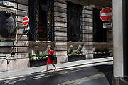 A lady in a red dress walks on Finch Street, a narrow medieval-era lane in the City of London, the capitals historic financial district, on 2nd August 2018, in London, England.