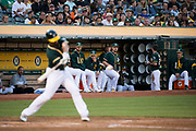 The Oakland Athletics watch as Oakland Athletics shortstop Marcus Semien (10) makes contact with a San Francisco Giants pitch at Oakland Coliseum in Oakland, California, on August 1, 2017. (Stan Olszewski/Special to S.F. Examiner)
