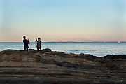 couple photographing each other Tokyo Bay Yokosuka with in the distance Chiba prefecture
