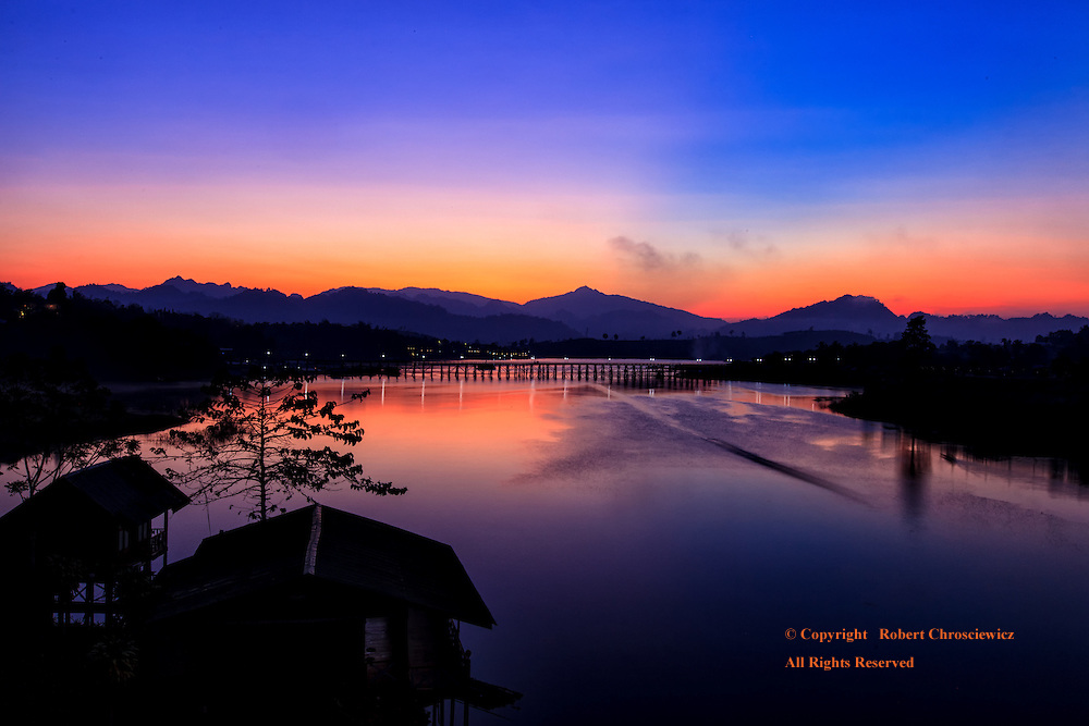 Mornings' Clarity: The pending sunrise finds all calm, with the dark of the night gently surrendering to the light of day that is reflected in the lake below, San Khla Buri Thailand.
