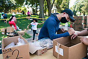 Mariano Espinoza, a Latino Community Specialist with the City of Minneapolis, distributes meat to local residents during a pop up grocery event at Powderhorn Park in Minneapolis, Minnesota, U.S., on Friday, July 24, 2020. Photographer: Ben Brewer/Bloomberg