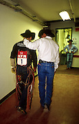 """14 DECEMBER 2002 - LAS VEGAS. NEVADA. USA: Jesse Bail, a bull rider from Camp Crook, SD, talks to Mike Rich, a medic with the Justin Sports Medicine Team, after being thrown from a bucking bull at the National Finals Rodeo in Las Vegas, NV, Dec 14, 2002. The NFR is the """"super bowl"""" of rodeo and draws hundreds of thousands of rodeo fans to Las Vegas for ten days every December. The rodeo is held at the Thomas and Mack center, which sells out for all ten performances. Other cowboy and western themed events take place around Las Vegas.  PHOTO BY JACK KURTZ"""
