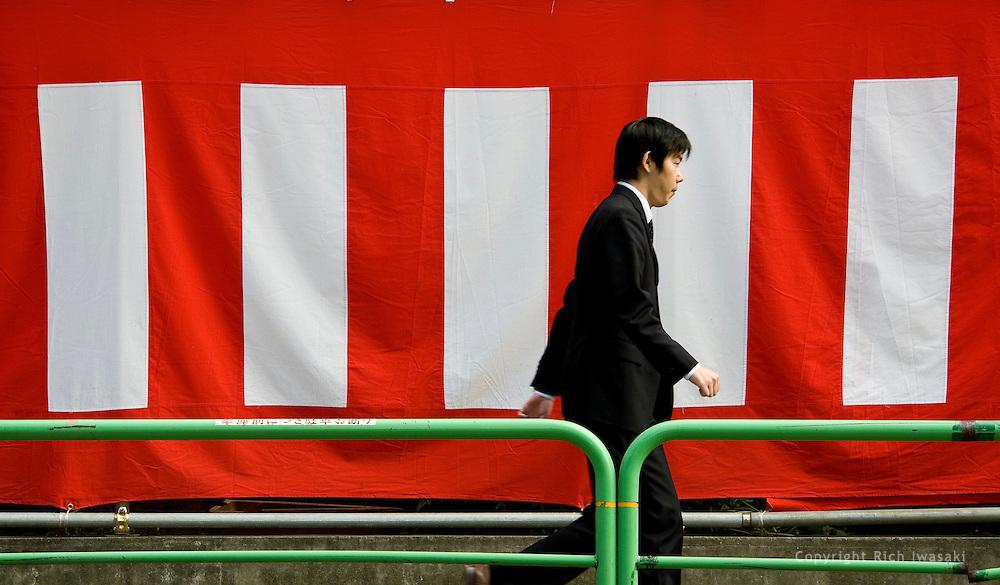 Pedestrian walks past banner near Fukagawa Fudo-do temple, Monzen Nakacho district, Tokyo, Japan