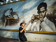 20 OCTOBER 2016 - BANGKOK, THAILAND:  A woman prays for the late Bhumibol Adulyadej, the King of Thailand, at a mural of the King in front of Silpakorn University. The King was an avid photographer and is frequently pictured with a camera in his hands. The King died Oct. 13, 2016. He was 88. His death came after a period of failing health. Bhumibol Adulyadej was born in Cambridge, MA, on 5 December 1927. He was the ninth monarch of Thailand from the Chakri Dynasty and is also known as Rama IX. He became King on June 9, 1946 and served as King of Thailand for 70 years, 126 days. He was, at the time of his death, the world's longest-serving head of state and the longest-reigning monarch in Thai history.      PHOTO BY JACK KURTZ