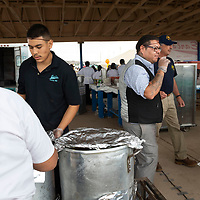 Zander Yazzie, in the black and grey vest, works to keep the kitchen running for the free bbq held by Earl's out of Gallup during the Navajo Nation Fair at the Navajo Nation Fairgrounds in Window Rock, AZ.