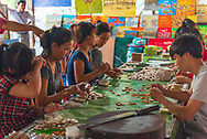 Mekong River, Vietnam -- March 20, 2016 Workers in a small home based factory along the Mekong River making candy.