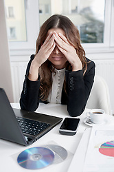 Young over-burdened businesswoman at her workplace