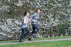 © Licensed to London News Pictures 13/04/2021. Greenwich, UK. Two women running together. People enjoying the sunny weather and exercising in Greenwich Park, London as coronavirus lockdown restrictions continue to ease in the UK. Photo credit:Grant Falvey/LNP