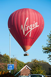 Virgin Balloon Flights hot air balloon appears very low over houses near Prospect Park, Reading, Berkshire, England, UK.