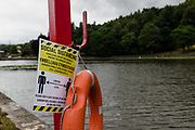 MERTHYR TYDFIL, Wales - 04 JUNE 2020 - Social distancing sign attached to a Lifebuoy and the lake in the background