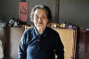 senior Japanese woman at entrance hall of house