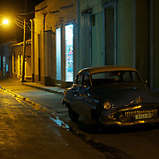 An old vintage car in the dark shadow of a lighted street in Trinidad, Cuba