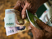 15 DECEMBER 2016 - PRACHINBURI, THAILAND: A man holds his 1,500 Baht cash disbursement outside a government credit union in Prachinburi, Thailand. The Thai government said people who earn 30,000 Baht (about $857 US) or less per year are entitled to a 3,000 Baht cash payment (about $85.7 US) and those who earn 30,000 Baht to 100,000 Baht (about $2,857 US) per year are entitled to a 1,500 Baht (about $42.8 US) cash payment. The plan is meant to help low income people, especially the rural poor. Government banks in rural areas offering the disbursement have been crowded with people seeking their payments this week.      PHOTO BY JACK KURTZ   Social Safety Net