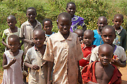 Portrait of a group of young African children on the side of the road waiting for a treat, Kenya, Africa