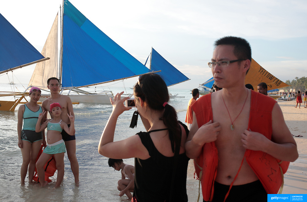 Asian tourists prepare for a boat ride at White Beach,  Boracay Island, the Philippines on October 4, 2008, Photo Tim Clayton..Asian tourists at White Beach, Boracay Island, the Philippines...The 4 km stretch of White beach on Boracay Island, the Philippines has been honoured as the best leisure destination in Asia beating popular destinations such as Bali in Indonesia and Sanya in China in a recent survey conducted by an International Travel Magazine with 2.2 million viewers taking part in the online poll...Last year, close to 600,000 visitors visited Boracay with South Korea providing 128,909 visitors followed by Japan, 35,294, USA, 13,362 and China 12,720...A popular destination for South Korean divers and honeymooners, Boracay is now attracting crowds of tourists from mainland China who are arriving in ever increasing numbers. In Asia, China has already overtaken Japan to become the largest source of outland travelers...Boracay's main attraction is 4 km of pristine powder fine white sand and the crystal clear azure water making it a popular destination for Scuba diving with nearly 20 dive centers along White beach. The stretch of shady palm trees separate the beach from the line of hotels, restaurants, bars and cafes. It's pulsating nightlife with the friendly locals make it increasingly popular with the asian tourists...The Boracay sailing boats provide endless tourist entertainment, particularly during the amazing sunsets when the silhouetted sails provide picture postcard scenes along the shoreline...Boracay Island is situated an hours flight from Manila and it's close proximity to South Korea, China, Taiwan and Japan means it is a growing destination for Asian tourists... By 2010, the island of Boracay expects to have 1,000,000 visitors.
