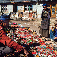 A trekker and her young son look at a merchant's trinkets in the Khumbu region of Nepal 1986.