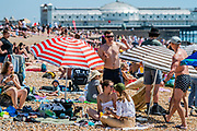 It is sunny and people come to the beach and the seaside at Brighton, during Bank holiday Monday. It is busy but still plentyu of room for social distancing. The eased 'lockdown' continues for the Coronavirus (Covid 19) outbreak.