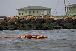 06 June 2010. Barataria Bay to Grand Isle, Jefferson/Lafourche Parish, Louisiana. <br /> Oil soaked boom floats ahead of oil soaked rocks on Grand Isle. The ecological and economic impact of BP's oil spill is devastating to the region. Oil from the Deepwater Horizon catastrophe is evading booms laid out to stop it thanks in part to the dispersants which means the oil travels at every depth of the Gulf and washes ashore wherever the current carries it. The Louisiana wetlands produce over 30% of America's seafood and are the most fertile of their kind in the world.<br /> Photo; Charlie Varley/varleypix.com