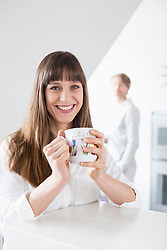 Portrait of woman with cup of coffee while man in background