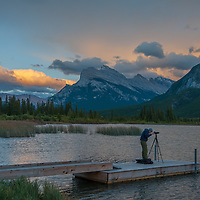 A photographer shoots a sunset over the Canadian Rockies and  Vermillion Lakes in Banff National Park, Alberta, Canada. Behind are Mount Rundle and Sulphur Mountain (R.)