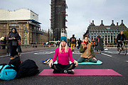Climate Change protesters practise yoga on Westminster Bridge on 7th October, 2019 in London, Untited Kingdom. Extinction Rebellion plan to occupy 12 sites situated around key Government locations around Westminster for two weeks to protest against climate change.