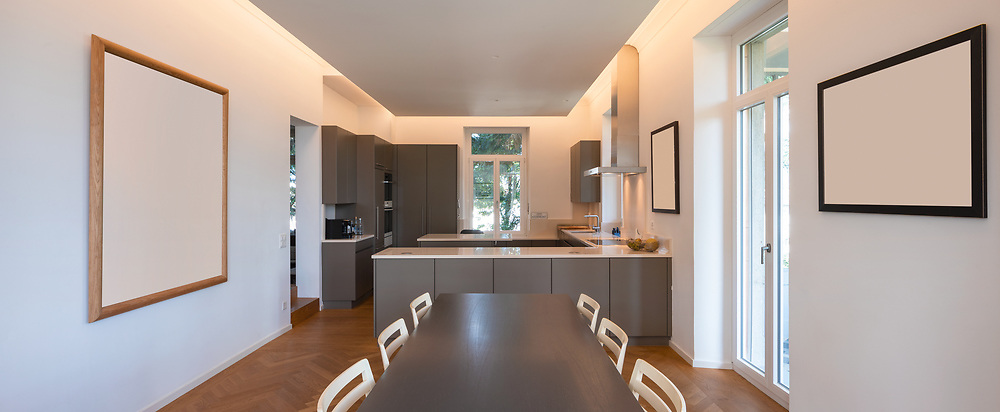 Modern kitchen in a period villa with window and parquet. Large table with chairs and bright windows. Nobody inside
