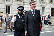 A police officer escorts Jacob Rees-Mogg MP, Leader of the House of Commons to his car as he leaves the Cabinet office in Whitehall, London, United Kingdom on 20th August 2019.