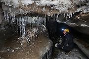 Kiya Riverman admires delicate stalactites in an ice cave in Larsbreen, Svalbard.