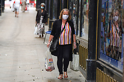 © Licensed to London News Pictures. 13/08/2020. Oldham, UK. A woman wears a face covering as she carries her shopping in Oldham this afternoon.  In recent weeks, the town of Oldham has seen a rapid increase in new coronavirus cases. Photo credit: Ioannis Alexopoulos/LNP