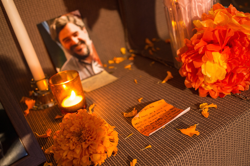 New York, NY, October 31, 2013. A photograph and a handwritten note on the altar. In the foreground is a traditional orange marigold.