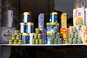 Cans of assorted foodstuffs and produce on sale in a corner shop window, on 27th June 2021, in Holt, Norfolk, England.