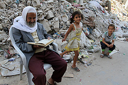 01.07.2015, Rafah, PSE, Nahostkonflikt zwischen Israel und Palästina, im Bild Wiederaufbau nach dem Krieg im vergangenen Sommer // A Palestinian man reads the holy book Quran, near the rubble of El-Farouk mosque, which was destroyed during the 50-day war between Israel and Hamas in the summer of 2014, Palestine on 2015/07/01. EXPA Pictures © 2015, PhotoCredit: EXPA/ APAimages/ Abed Rahim Khatib<br /> <br /> *****ATTENTION - for AUT, GER, SUI, ITA, POL, CRO, SRB only*****