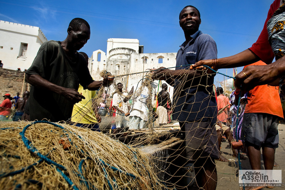 """Fishermen clean their nets after returning from sea in Cape Coast, roughly 120km west of Ghana's capital Accra on Thursday April 9, 2009. """"Local jobs are collapsing"""" says the Ministry of Fisheries' Isiah Amoukouandoh. """"It's a difficult balance for the government because foreign trawlers contribute to government funds. If the trawlers stuck to regulations, there would be less of a problem. But they are fishing in the waters reserved for the local fishermen, stealing their fish."""""""