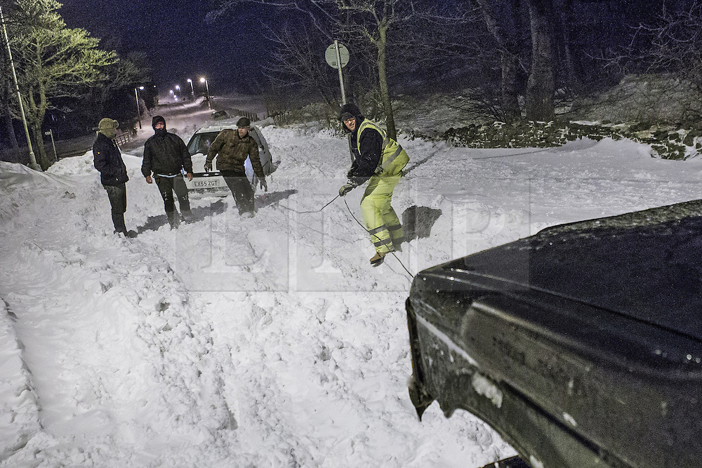 © Licensed to London News Pictures . 24/03/2013 . Burnley , UK . A good samaritan with a 4x4 and a winch helps a stranded driver on Halifax Road as snow is blown across the road from a nearby field . Snowdrifts are making roads impassable around Burnley overnight (23rd/24th March) as high winds blow snow across roads . Plummeting temperatures and treacherous conditions are reported to have taken the life of a man named locally as Gary Windle . Lancashire Police reported finding a 27 year old man dead in deep snow yesterday (23rd March) afternoon . Photo credit : Joel Goodman/LNP