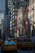 Flags of the United States blow in the wind displayed outside the Rockefeller Centre buildings, 610 5th Avenue, Midtown, Manhattan, New York City, New York, United States of America.  Busy traffic drives along 5th Avenue including the classic New York yellow taxi.