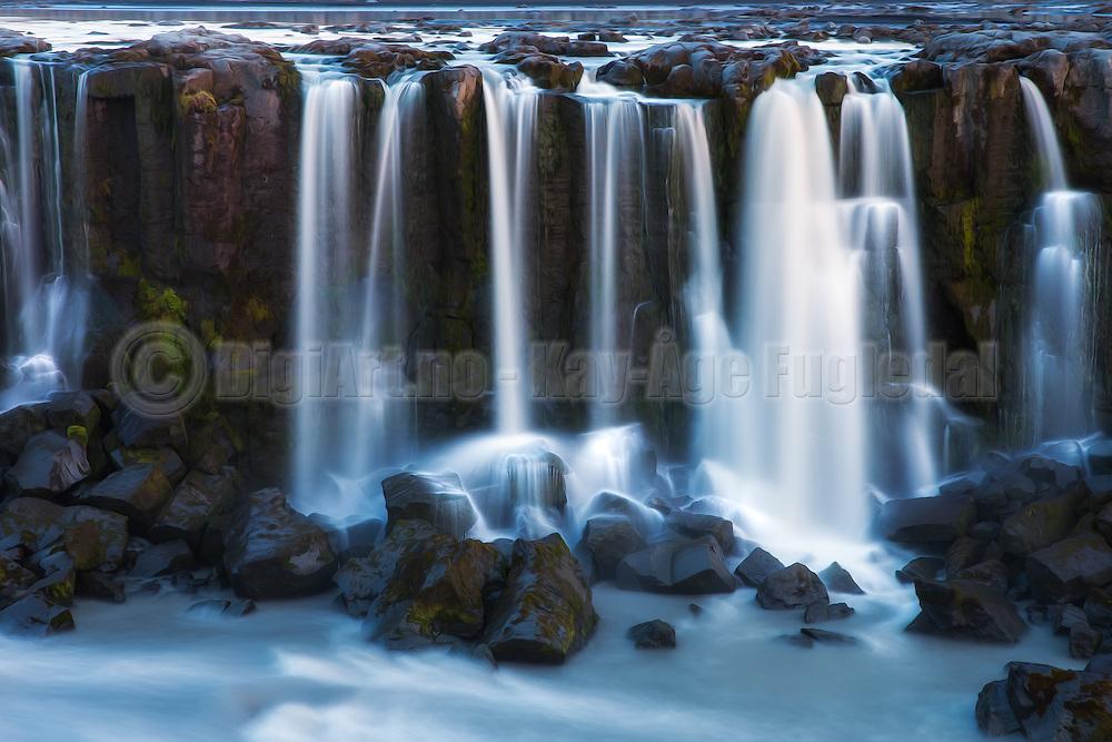 Selfoss is a waterfall in the river Jökulsá á Fjöllum in the north of Iceland which drops over some waterfalls about 30 km before flowing into Öxarfjörður, a bay of the Arctic Sea | Selfoss er en foss i nord Island i elven Jökulsá á Fjöllum, som strekker seg ca 30 kilometer før den renner ut i fjorden Öxarfjörður i Ishavet.