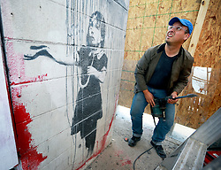 21 February 2014. New Orleans, Louisiana.<br /> A considerably irrational and unpleasant 'private art handler' from Los Angeles, giving his name only as Chris chops an original Banksy known as 'Rain Girl' from the wall of an old abandoned store in New Orleans on the corner of North Rampart and Kerlerec streets. Chris claims the artwork is to be shipped to London for a Tate Modern retrospective of Banksy's work in April. Chris also claims the artwork will be re-installed at its current location once the exhibition is finished - a claim local residents seriously doubt.<br /> Photo; Charlie Varley/varleypix.com