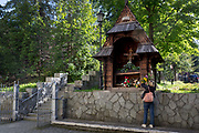 A lady churchgoer attends to flowers at a traditional southern Polish Catholic shrine outside St. Adalbert Bishop And Martyr Church, on 21st September 2019, in Szczawnica, Malopolska, Poland.