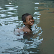 A boy swiming in the dirty water of the dhobiwala tank. The small tank collecting water from the gutters running along the railway tracks provides a livelihood to a small community of dhobiwalas (laundrymen), who wash the clothes, sheets and blankets of the local community.