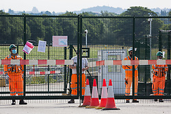 HS2 workers stand at a gate to a construction site for the high-speed rail link on 26th June 2020 in Harefield, United Kingdom. They were observing activists from HS2 Rebellion and Extinction Rebellion UK taking part in a 'Rebel Trail' hike along the route of the high-speed rail link in protest against its environmental impact and to question the viability of the £100bn+ project.