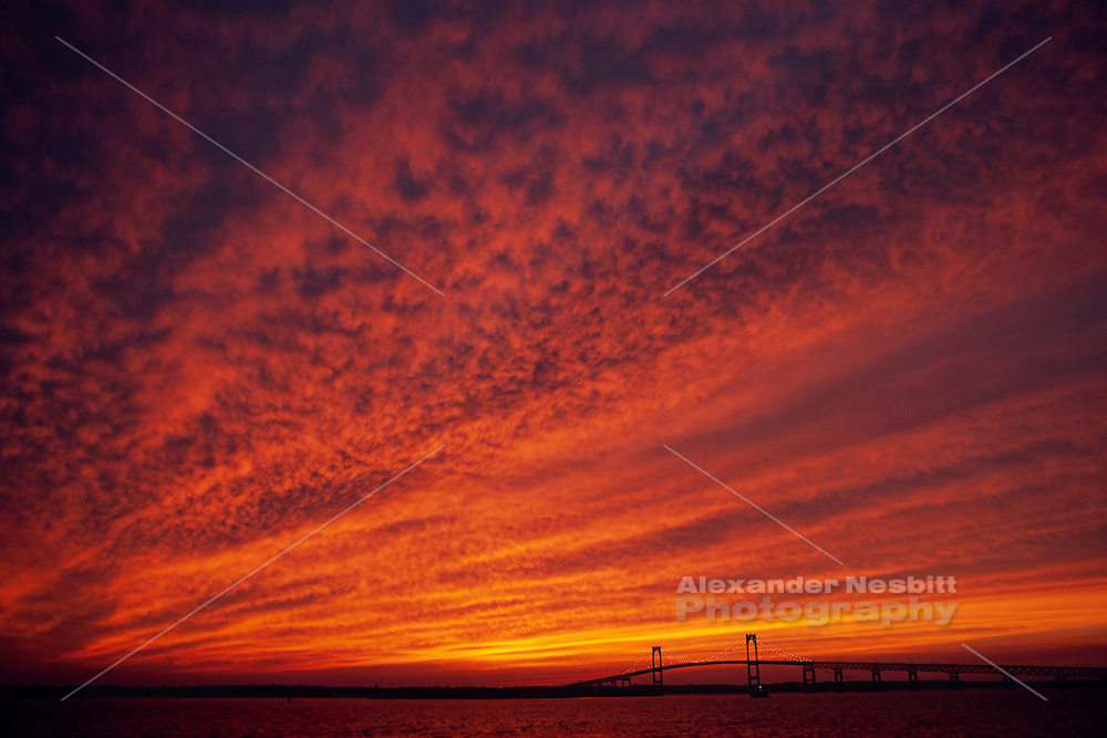USA, Newport, RI - Sunset paints low clouds over Narragansett bay and Newport bridge. Super wide angle view of sky.