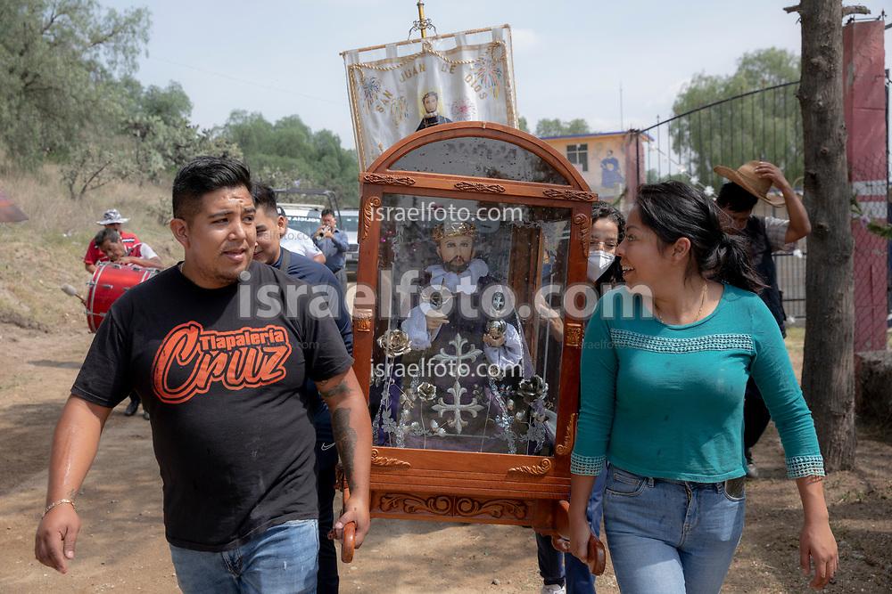 02 junio 2021, Tultepec, Estado de México. Una pareja carga hacia su taller de pirotecnia una imagen de San Juan de Dios durante la celebración anual de ese santo en los talleres de La Saucera