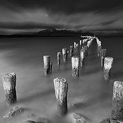 A black and white image of wooden pillars of an old pier standing motionless against a turbulent sky and sea shore turned smooth in a 2 minute long exposure.Puerto Natales, Patagonia, Chile.