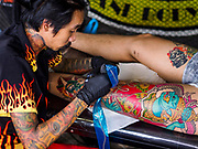 "28 OCTOBER 2018 - BANGKOK, THAILAND: A man gets a tattoo of Hanuman, the ""Monkey God"" on his thigh at the 2018 MBK Center Tattoo Fest. Tatoo artists from around the world came to participate in the festival, which featured both modern (using tattoo machines) and traditional methods (done by hand with long needles) of tattooing.   PHOTO BY JACK KURTZ"