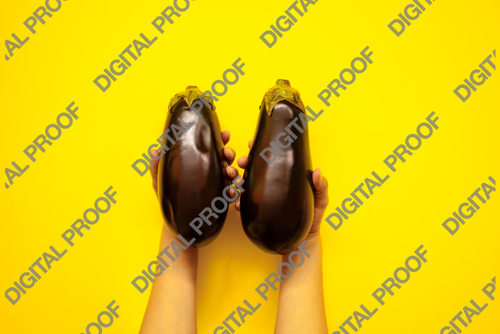 Top view of woman hands holding a pair of aubergines in studio over a yellow background - flatlay look