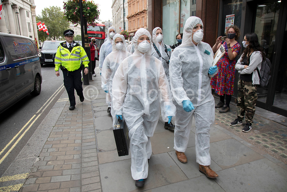 Extinction Rebellion 'crime scene investigators' in white suits and masks put up climate crime scene tape to investigate areas of ecocide in a performance arrive outside the Brazilian Embassy on 7th September 2020 in London, United Kingdom. The 20 investigators were protesting at the Brazilian government's alleged involvement in ecocide in the Amazon. Extinction Rebellion is a climate change group started in 2018 and has gained a huge following of people committed to peaceful protests. These protests are highlighting that the government is not doing enough to avoid catastrophic climate change and to demand the government take radical action to save the planet.