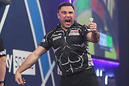 Gerwyn Price hits a double and celebrates winning the first set during the William Hill World Darts Championship Final at Alexandra Palace, London, United Kingdom on 3 January 2021.
