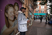 Young busker wearing a reflective snorkel coat playing the saxophone in Birmingham, United Kingdom.